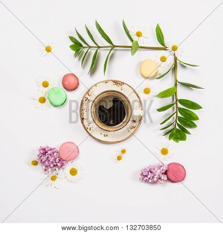 Coffee french cookies macaroons spring flowers. Floral flat lay. Minimal concept