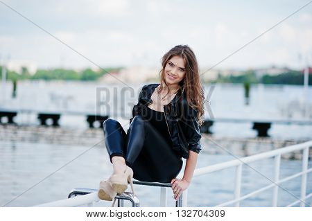 Portrait Of Gorgeous Sexy Brunette Girl Model Sitting On The Railing Of The Pier