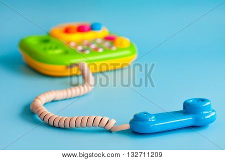 Children's toy phone with a tube of plastic on a blue background. The handset is removed from the machine. Listen beeps. Copy space.