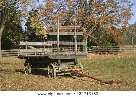 An old wooden wagon on a farm in autumn with a fence. Taken at Carraige Hill Dayton Ohio