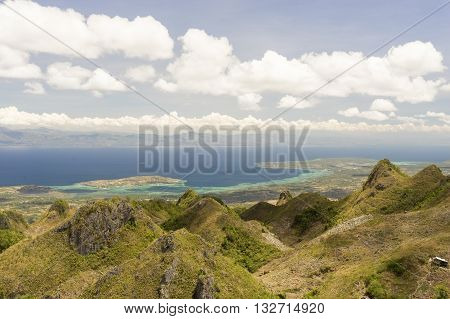 View from mountains to the tropical sea between philippine island under cloudy blue sky