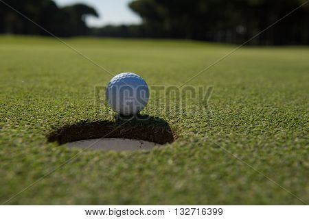 golf ball on edge of course hole representing achivement and success business concept