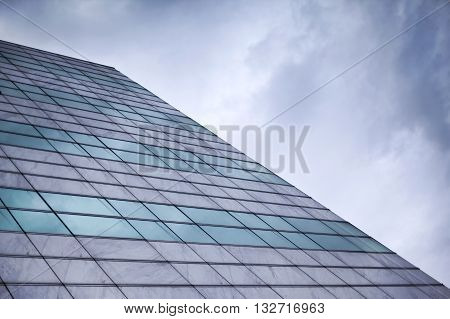 Glass wall of a buiding facade and cloudy sky