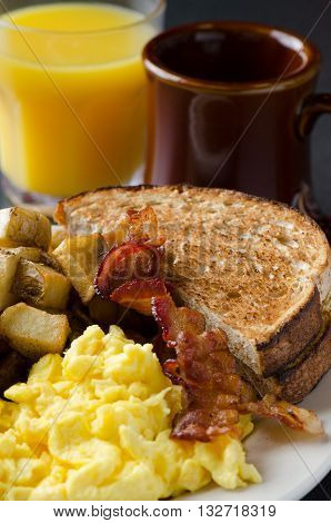 Traditional American breakfast scrambled eggs, toast, bacon, and hash-browns.