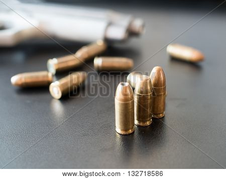 11mm bullets and short gun on black background. (selective focus)