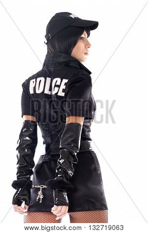 Portrait of beautiful sexy policewoman with handcuffs in a black uniform isolated on white.