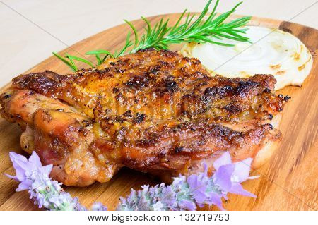 barbecued grilled boneless chicken thigh and grilled onion slice with fresh rosemary and lavender garnish on a plank board and neutral background