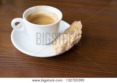 espresso in white demi-tasse with almond and lemon peel biscotti on a dark brown wooden table