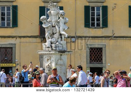 Pisa Italy - June 29 2015: Tourists near the fountain with angels on Piazza dei Miracoli. Province Pisa Tuscany region of Italy
