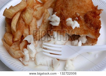 A plate of traditional English fish and chips with fork