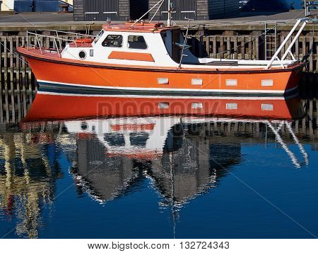 Reflection of a modern motorboat in the sea water of a marina
