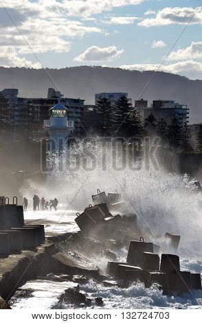 Big waves breaking over Wollongong harbor breakwall and people near the lighthouse