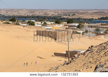 Kids running on sandy desert at Nubian village, Egypt.