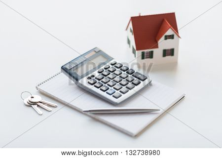 mortgage, real estate and property concept - close up of home model, house keys, calculator and notebook with pen