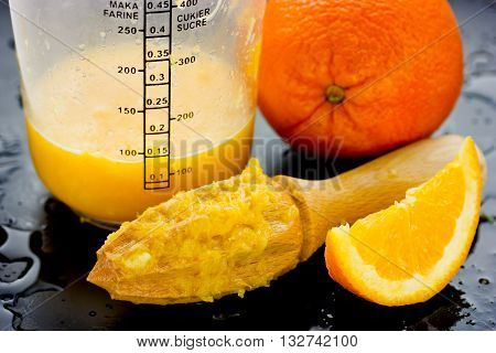 Homemade fresh orange juice whole and sliced orange wooden hand squeezer on a black table with drops of juice