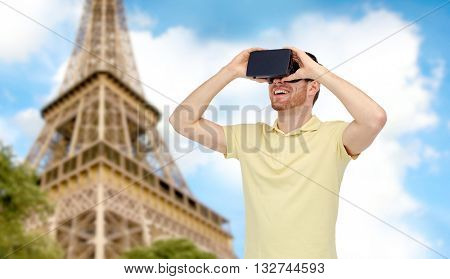 3d technology, virtual reality, travel, entertainment and people concept - happy young man with virtual reality headset or 3d glasses over paris eiffel tower background
