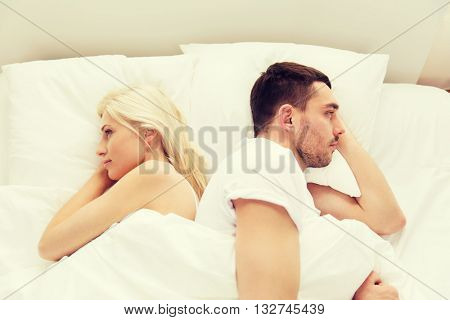 people, relationship difficulties, conflict and family concept - unhappy couple lying back to back in bed at home