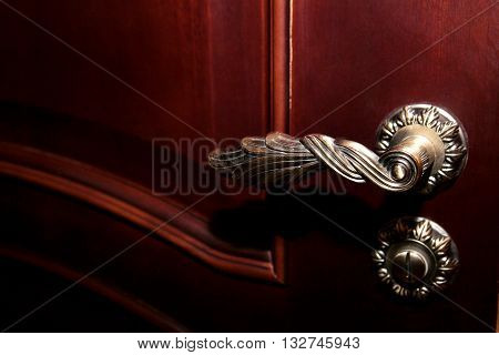 Part of brown wooden door with a metal handle and a beautiful castle