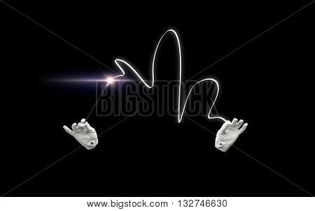 performance, illusion, circus, show concept - magician hands in gloves with illuminating magic wand showing trick over black background
