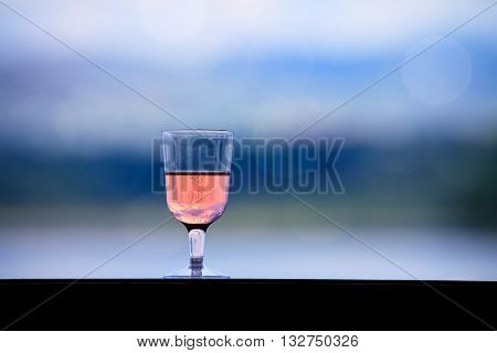 glass with rose wine over the bokeh nature background