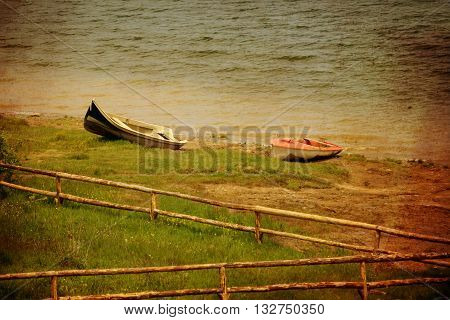 two boats and wooden fence in lake beach vintage grunge style