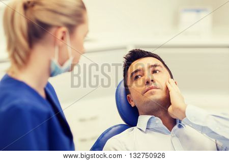 people, medicine, stomatology and health care concept - male patient with toothache complaining to female dentist at dental clinic office