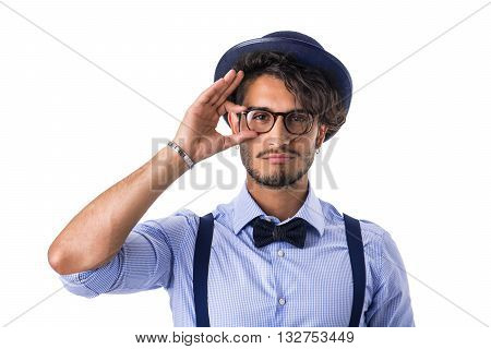 Portrait of brunette young man in glasses, hat, bow-tie, suspenders and shirt looking at camera. Studio shot, isolated on white