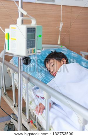Asian Boy Lying On Sickbed With Infusion Pump Intravenous Iv Drip.
