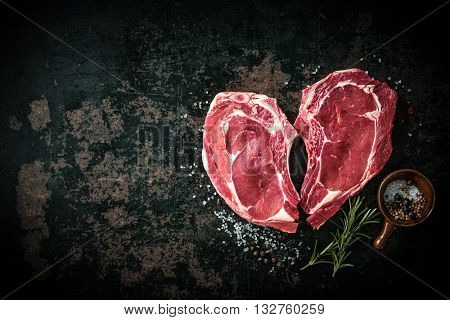 Heart shape raw fresh veal meat steaks with rosemary, pepper and salt on dark background