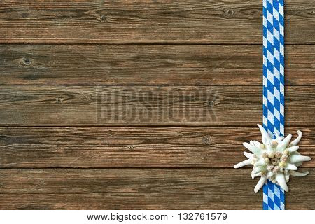Oktoberfest background with edelweiss and Bavarian ribbon on wooden background