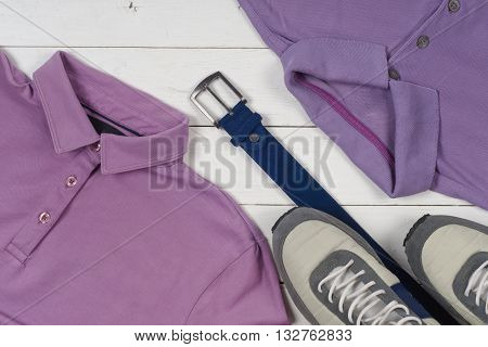 set of men's clothing and shoes on wooden background. Sports T-shirt and sneakers in bright colors. Top view. Copy space for text.