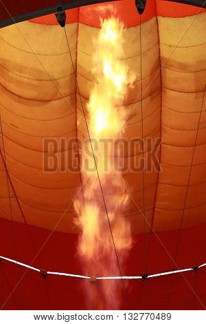 a hot air balloon ready to take off by firing up a burner to heat the air inside the nylon envelope