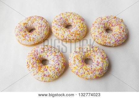 Donuts stacked in the form of Olimpidy symbol: the five rings. Crumpet for tea. Tasty food cakes. Classic cakes: fried doughnuts glazed with caramel. Nutritious dish that promotes obesity.