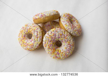 A mound of donuts. Crumpet for tea. Tasty food cakes. Delicious classic cakes: fried doughnuts glazed with caramel. Nutritious dish that promotes obesity.