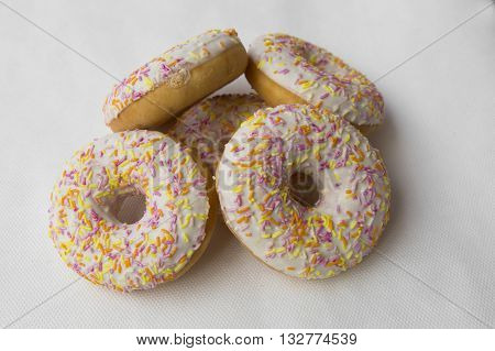 Mound of donuts. Crumpet for tea. Tasty food cakes. Delicious classic cakes: fried doughnuts glazed with caramel. Nutritious dish that promotes obesity.