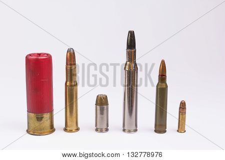 Line of bullets and shotgun shell on white background