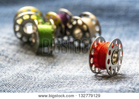 Rolls of sewing thread and blue jeans background with natural lighting.