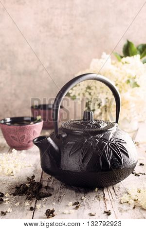 Cast iron black teapot with healthy medicine green tea with elder flower on old white wooden tafel with elder flower branches. Copy space.
