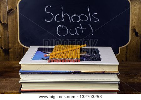 stack of books and pencils on wood background in front of chalkboard written schools out
