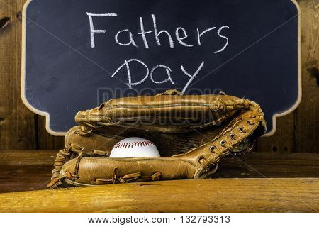 baseball bat glove and ball on wood background in front of chalkboard written fathers day