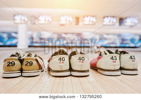 Three pairs of shoes for bowling at alley