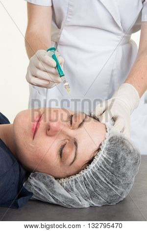 Doctor female giving botox injections to a female patient