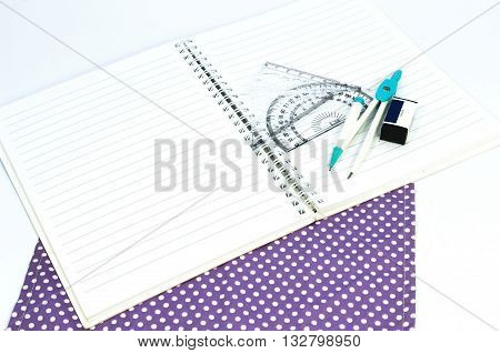 Empty white paper notebook with ruler protractor angle triangle square on the white background.