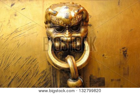 A golden lion face and rings on a large golden urn within the forbidden city in Beijing China.
