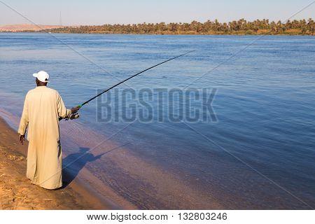 NILE, EGYPT - FEBRUARY 9, 2016: Local man fishing on the shore of Nile.