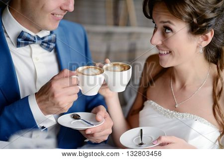 Wedding Couple Indoors Is Drinking Coffee. Beautiful Model Girl In White Dress. Man In Suit. Beauty