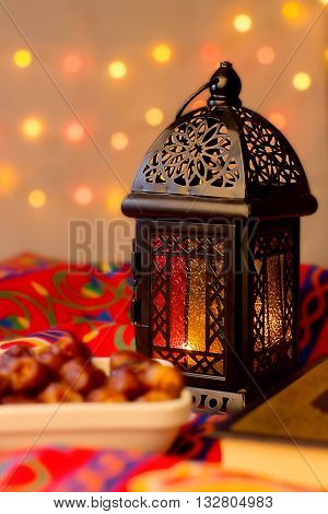 Ramadan Background - Lantern dish of dates and Quraan on Ramadan colorful fabrics