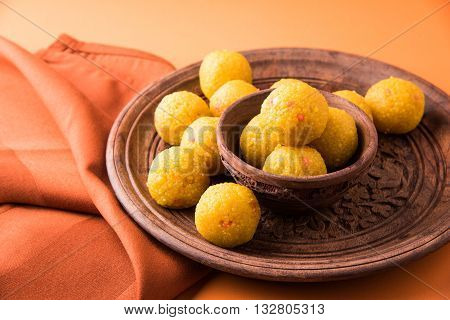 Indian sweet bundi laddu or motichur laddu served in a carved woodel bowl and plate with drapery or table napkin, selective focus poster