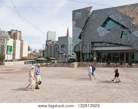 Melbourne - February 23 2016: People and tourists walk at Federation Square on a hot day near the station Flinders Street Station February 23 2016 Melbourne Australia