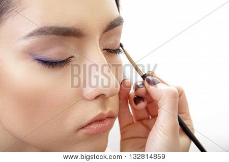 Stylist hand applying eyes make-up to the eyelids of a young beautiful model.